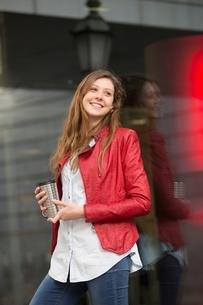 Woman holding warm drink in streetの写真素材 [FYI03539607]