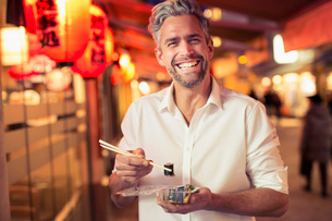Man holding sushi with chopstick looking at camera laughingの写真素材 [FYI03539637]