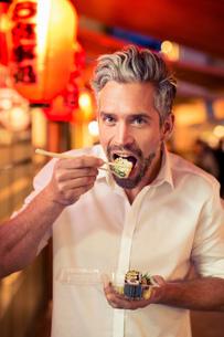 Man looking at camera using chopsticks to eat sushiの写真素材 [FYI03539638]