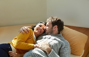 Mid adult couple on window seat face to face laughingの写真素材 [FYI03539844]