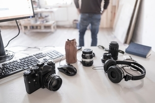 Camera, accessories and computer on desk, photographer in backgroundの写真素材 [FYI03540194]