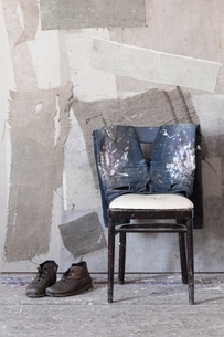 Pair of boots, dirty jeans on chair, painted wallの写真素材 [FYI03540197]