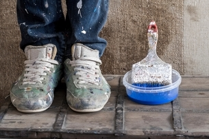 Legs wearing dirty shoes beside plastic container with paint brushの写真素材 [FYI03540203]