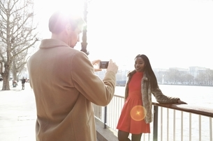 Couple standing beside river, young woman leaning against railings, man taking photograph of herの写真素材 [FYI03540246]