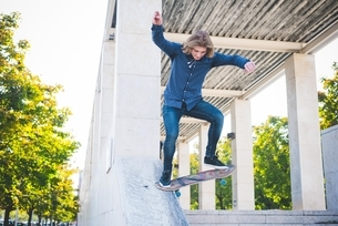 Young male urban skateboarder skating down concrete structureの写真素材 [FYI03540284]