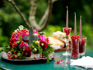 Flower arrangement with glasses of redcurrants and candles on garden tableの写真素材 [FYI03540424]