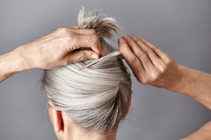 Rear view of woman styling gray hair into bunの写真素材 [FYI03540444]