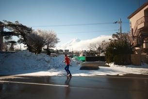 Mature man running on road in winter, Lake Kawaguchiko, Mount Fuji, Japanの写真素材 [FYI03540574]