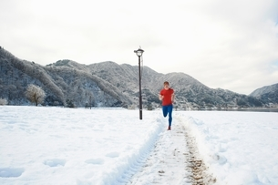 Male runner running along snow covered tracks, Lake Kawaguchiko, Mount Fuji, Japanの写真素材 [FYI03540585]