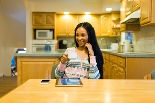 Young woman drinking coffee and using digital tablet  at kitchen tableの写真素材 [FYI03540615]
