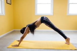 Young woman bending over in yoga pose on yoga matの写真素材 [FYI03540632]