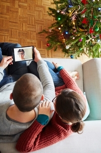 Overhead view of couple sitting on sofa making digital tablet video call at xmasの写真素材 [FYI03540972]