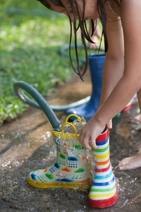 Girl filling wellies with water from hoseの写真素材 [FYI03541029]