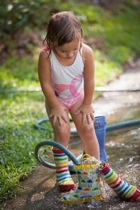 Child filling wellies with water from hoseの写真素材 [FYI03541030]
