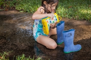 Girl filling wellies with waterの写真素材 [FYI03541032]