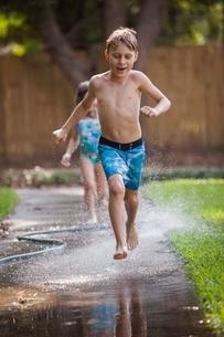 Children running in water on sidewalkの写真素材 [FYI03541037]