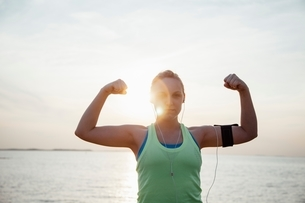 Woman wearing activity tracker, arms raised flexing muscles looking at cameraの写真素材 [FYI03541077]