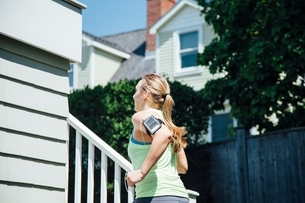Rear view of woman wearing activity tracker running up stairsの写真素材 [FYI03541085]