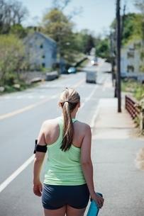 Rear view of woman wearing activity tracker carrying water bottle walking along roadの写真素材 [FYI03541088]