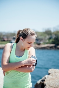 Woman wearing earbuds looking at activity tracker on armの写真素材 [FYI03541091]