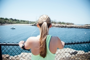 Rear view of woman wearing activity tracker holding wire fence looking at view of oceanの写真素材 [FYI03541092]