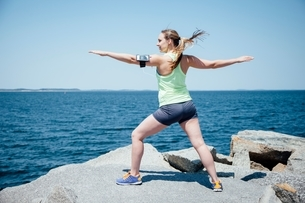 Full length rear view of woman wearing activity tracker on rocks by ocean, arms open exercisingの写真素材 [FYI03541093]