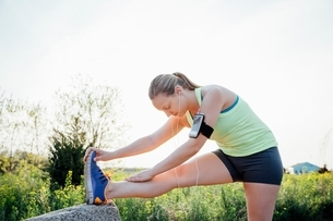 Woman wearing activity tracker bending forward touching toes stretchingの写真素材 [FYI03541101]