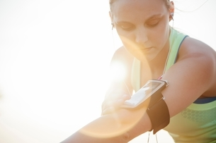 Woman wearing activity tracker on arm looking downの写真素材 [FYI03541102]