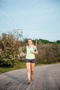 Full length front of woman wearing activity tracker jogging on roadの写真素材 [FYI03541103]