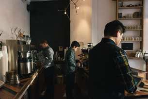 Manager and waiters preparing order at coffee shop counterの写真素材 [FYI03541332]
