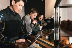 Manager and waiters preparing coffee order at coffee shop counterの写真素材 [FYI03541333]
