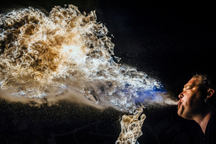 Low angle view of man fire breathingの写真素材 [FYI03541425]