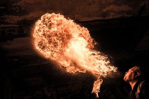 Low angle view of man fire breathingの写真素材 [FYI03541426]