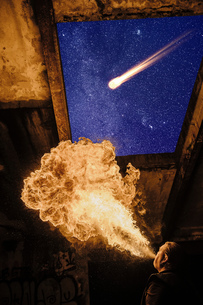 Low angle view of man fire breathing, meteor in starry night skyの写真素材 [FYI03541432]