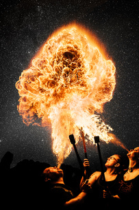 Performers fire breathing, starry night skyの写真素材 [FYI03541442]