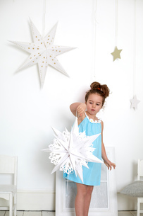 Girl with paper cut-out star against white wall with starsの写真素材 [FYI03541553]