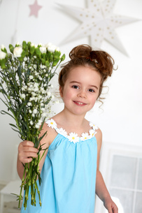Girl with carnations against white wall with starsの写真素材 [FYI03541554]