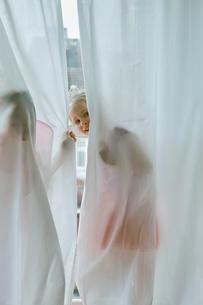 Girl peeking through curtainの写真素材 [FYI03541613]