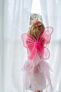 Girl in fairy costume peeking through curtainの写真素材 [FYI03541616]