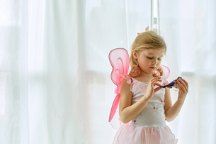 Girl in fairy costume playing by curtainの写真素材 [FYI03541617]