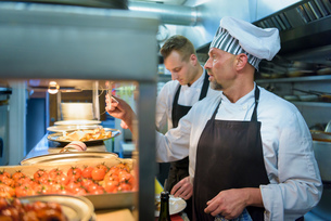 Chef checking order in traditional Italian restaurant kitchenの写真素材 [FYI03541767]