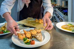 Chef arranging prawn and fish dish in traditional Italian restaurant kitchenの写真素材 [FYI03541784]