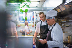 Chefs reading order in traditional Italian restaurant kitchenの写真素材 [FYI03541787]