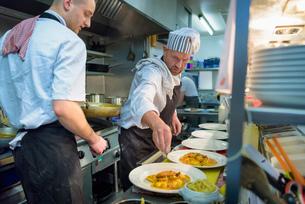 Chefs plating up lobster ravioli in traditional Italian restaurant kitchenの写真素材 [FYI03541790]