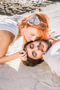 Head and shoulders of couple lying on beach face to faceの写真素材 [FYI03542102]