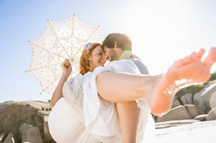Man carrying woman holding lace umbrella in arms face to face smilingの写真素材 [FYI03542114]