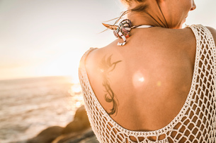Rear view of bird tattoo on womans shoulder on beach at sunset, Cape Town, South Africaの写真素材 [FYI03542185]