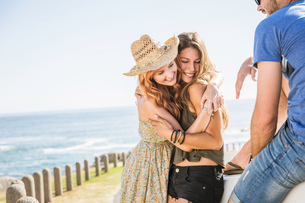 Mid adult friends hugging at coast, Cape Town, South Africaの写真素材 [FYI03542203]