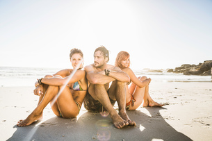 Three mid adult friends wearing swimwear sitting on beach, Cape Town, South Africaの写真素材 [FYI03542283]