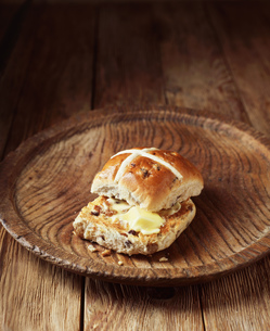 Buttered hot cross bun on vintage wooden plateの写真素材 [FYI03542408]